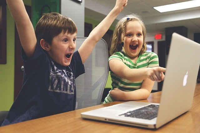 Two children celebrating at a computer. Source: https://pixabay.com/photos/children-win-success-video-game-593313/